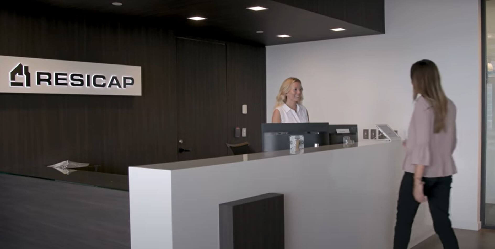 RESICAP Front desk receptionist greeting someone